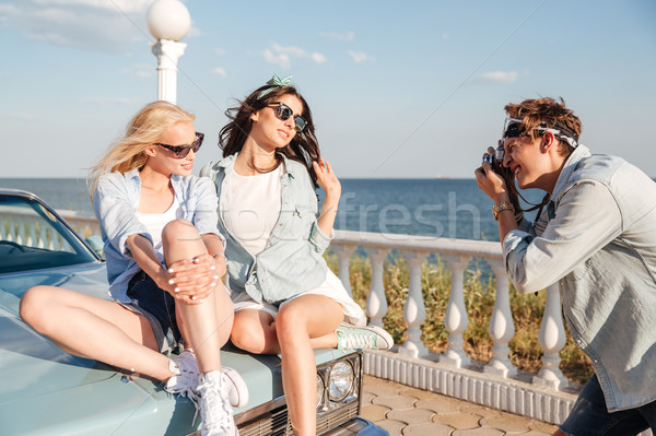 Man photographer taking photos of two women sitting on car Stock photo © deandrobot