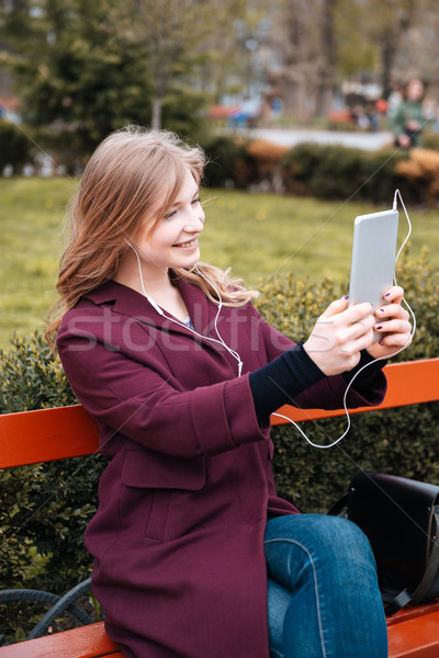 Happy woman listening to music and making selfie using tablet Stock photo © deandrobot