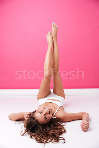 Woman in white swimwear lying on floor with raised legs Stock photo © deandrobot