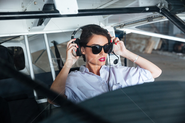 Woman pilot in headset ready to fly in small airplane Stock photo © deandrobot