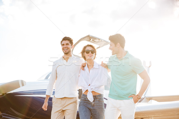 Happy young friends walking on runway in airport Stock photo © deandrobot