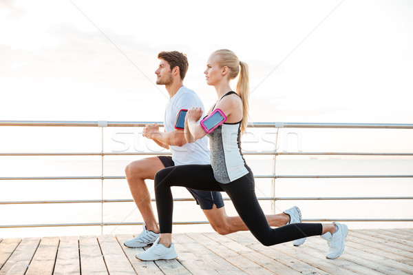 Sporty couple warming up before jogging at the beach Stock photo © deandrobot