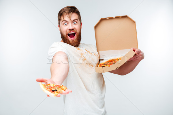 Cheerful bearded man giving slice of pizza Stock photo © deandrobot