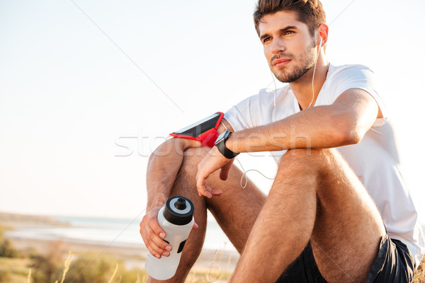 Handsome young sportsman sitting and holding bottle of water outdoors Stock photo © deandrobot