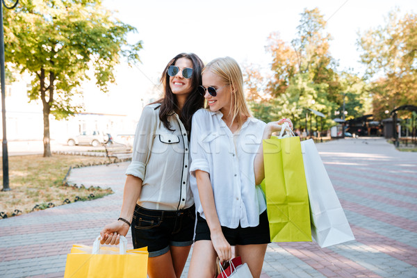 Two women shoppers in sunglasses holding shopping bags Stock photo © deandrobot