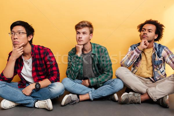 Három töprengő fiatal férfiak barátok gondolkodik másfelé néz Stock fotó © deandrobot