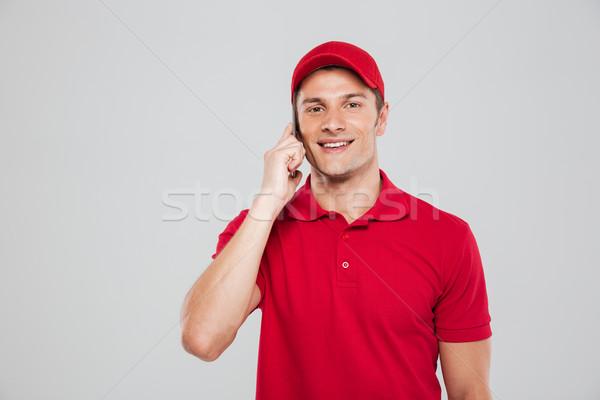 Beszél telefon néz kamera izolált szürke Stock fotó © deandrobot