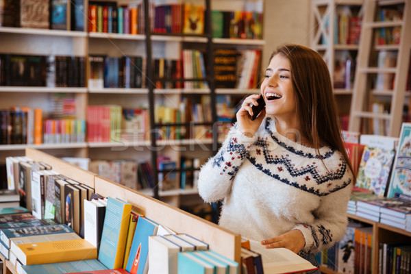 Woman talking on mobile phone while sitting in library Stock photo © deandrobot