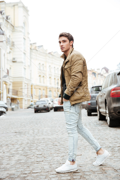 Young man walking on the street and looking aside. Stock photo © deandrobot
