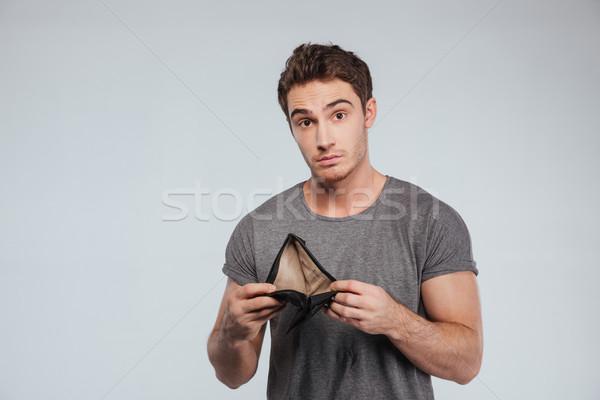 Ontdaan jonge man lege portemonnee witte Stockfoto © deandrobot