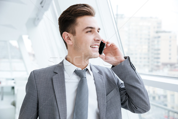 Happy Business man talking at phone near the window Stock photo © deandrobot