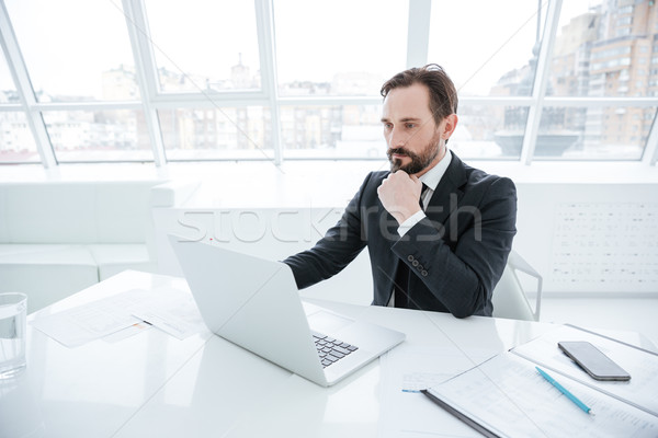 Stock photo: Side view of Serious Elderly business man by the table