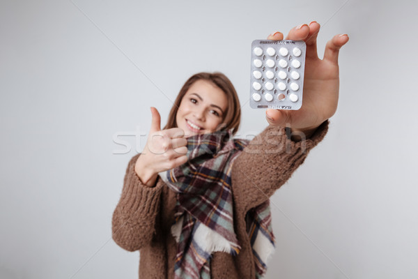 Sick young lady showing to camera medicine pills Stock photo © deandrobot