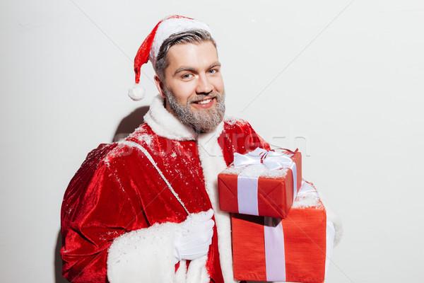 Derűs férfi mikulás ajándék zsák tart Stock fotó © deandrobot