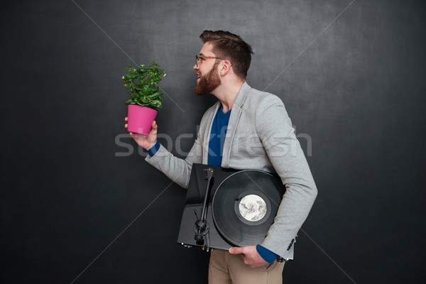 Profile of happy man with flowers in pot and turntable Stock photo © deandrobot