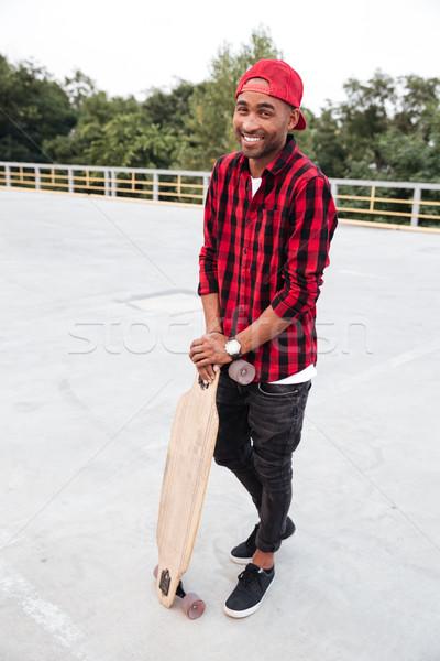 Cheerful dark skinned man holding his skateboard Stock photo © deandrobot