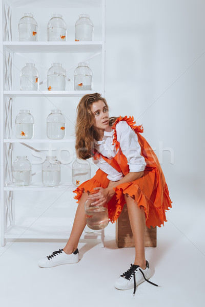 Woman with gold fish in jar sitting and looking back Stock photo © deandrobot