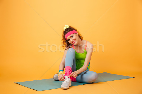 Smiling lovely young fitness woman sitting and tying shoelaces Stock photo © deandrobot