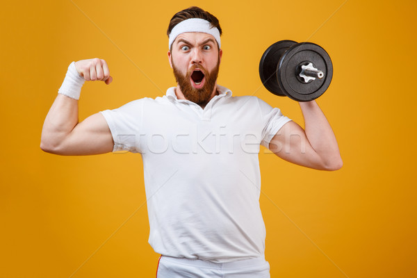 Screaming sportsman holding dumbbell and showing bicep Stock photo © deandrobot