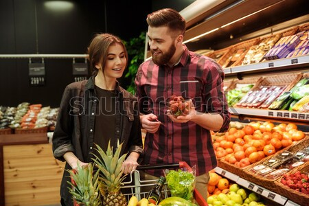 Loving couple in supermarket. Woman looking man holding beer. Stock photo © deandrobot