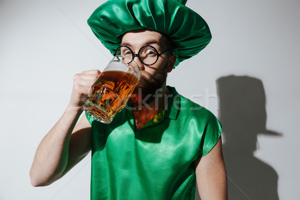Surprised man in st.patriks costume drinking beer Stock photo © deandrobot