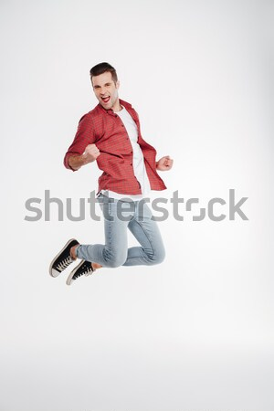 Vertical image of happy man jumping in studio Stock photo © deandrobot