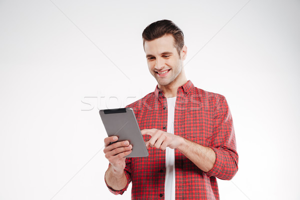 Smiling man using tablet computer Stock photo © deandrobot