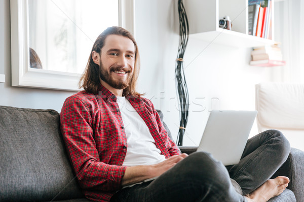 Smiling bearded young man sitting on couch and using laptop Stock photo © deandrobot