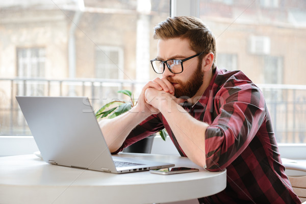 Handsome bearded young man using laptop computer. Stock photo © deandrobot