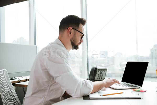 Yandan görünüş adam dizüstü bilgisayar kullanıyorsanız gömlek gözlük oturma Stok fotoğraf © deandrobot