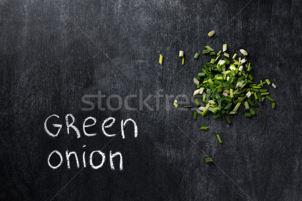Green onion over dark chalkboard background Stock photo © deandrobot