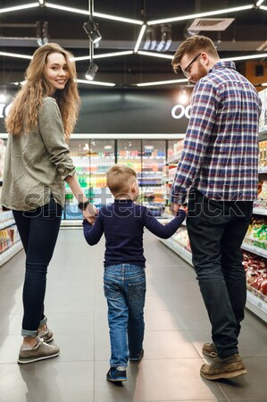 Vertical image of parents with son in shopping trolley Stock photo © deandrobot