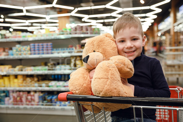Smiling boy in shopping trolley holding teddy bear Stock photo © deandrobot