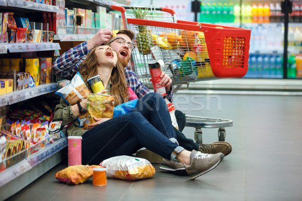 Cute couple trying to eat chips on the floor Stock photo © deandrobot