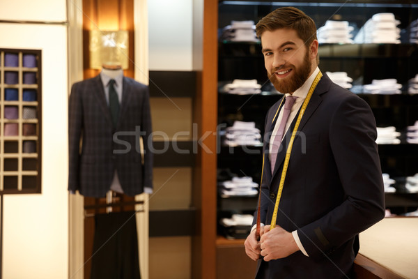 Smiling man standing in wardrobe with measure tape Stock photo © deandrobot