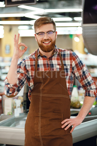 Cheerful cashier man on workspace in supermarket shop. Stock photo © deandrobot
