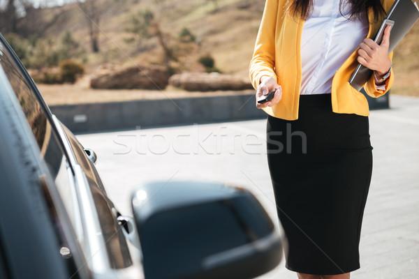 Businesswoman in yellow jacket closing the door of her car Stock photo © deandrobot