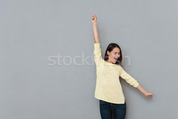 Derűs izgatott fiatal nő felemelt kezek áll kiált Stock fotó © deandrobot