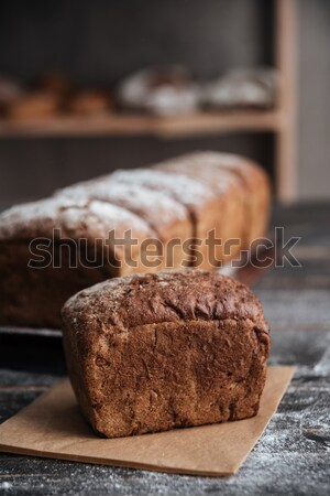 Bread with flour on dark wooden table Stock photo © deandrobot
