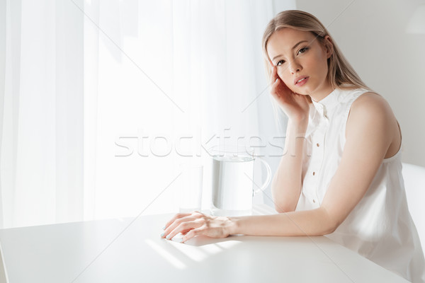 Serious blonde lady sitting indoors near water jug Stock photo © deandrobot