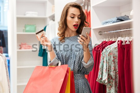 Young lady standing in clothes shop choosing dresses Stock photo © deandrobot