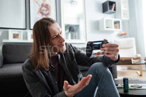 Confundirse hombre sesión casa jugar Foto stock © deandrobot