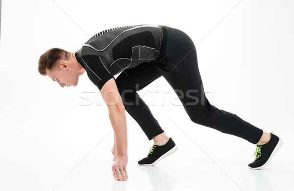 Portrait of a young concentrated sportsman ready to start running Stock photo © deandrobot