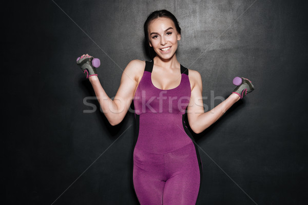 Portrait of a cheerful smiling fitness woman doing exercises Stock photo © deandrobot
