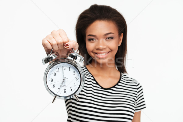 Portrait of a happy african teen girl showing alarm clock Stock photo © deandrobot
