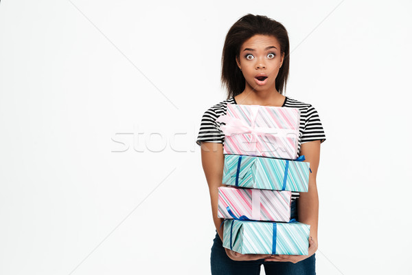 Surprised shocked african woman holding stack of present boxes Stock photo © deandrobot