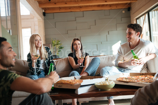 People with pizza, wine and beer sitting and talking Stock photo © deandrobot