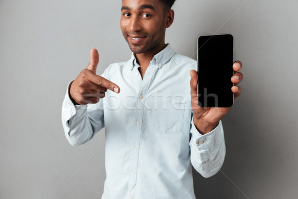 Excited man pointing finger at blank screen mobile phone Stock photo © deandrobot