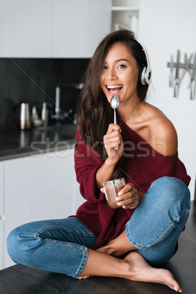 Laughing young asian woman in headphones eating dessert Stock photo © deandrobot