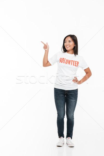 Portrait of a pretty joyful asian woman in volunteer t-shirt Stock photo © deandrobot